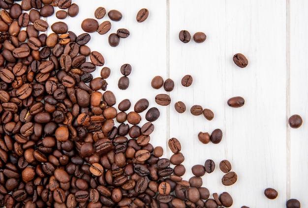 白い木製の背景に分離されたダークローストコーヒー豆のトップビュー