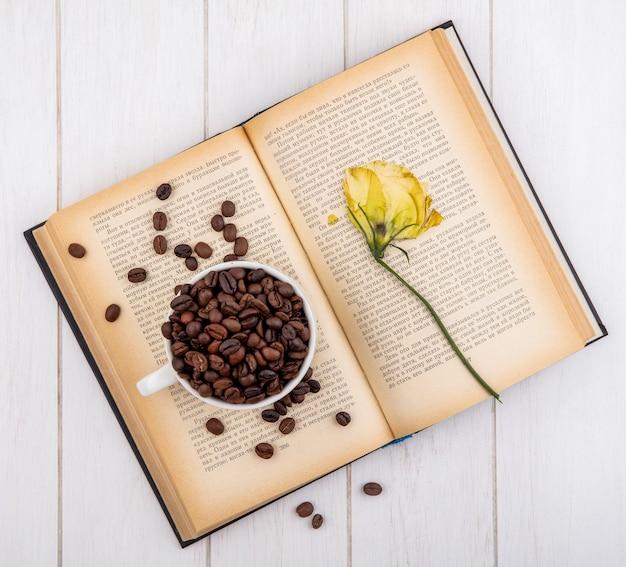 白い木製の背景に花と白いカップに暗いローストコーヒー豆のトップビュー