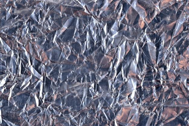 暗い銀色の箔の背景のテクスチャの上面図をクローズアップ