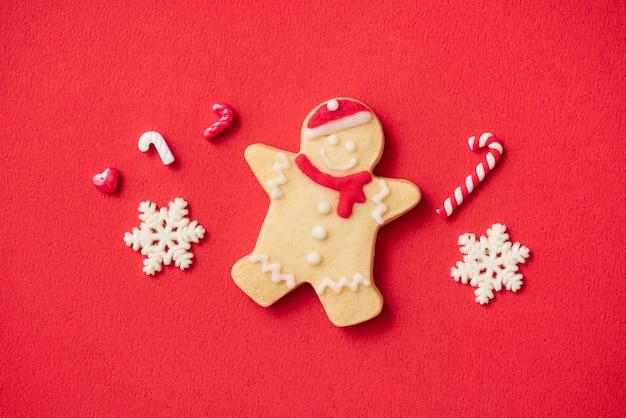 コピースペース、休日のお祝いの概念と赤いテーブルの背景に飾られたクリスマスジンジャーブレッドクッキーの上面図。