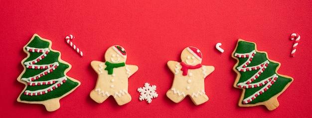 コピースペース、休日のお祝いの概念と赤いテーブルの背景に装飾が施された装飾されたクリスマスジンジャーブレッドクッキーの上面図。