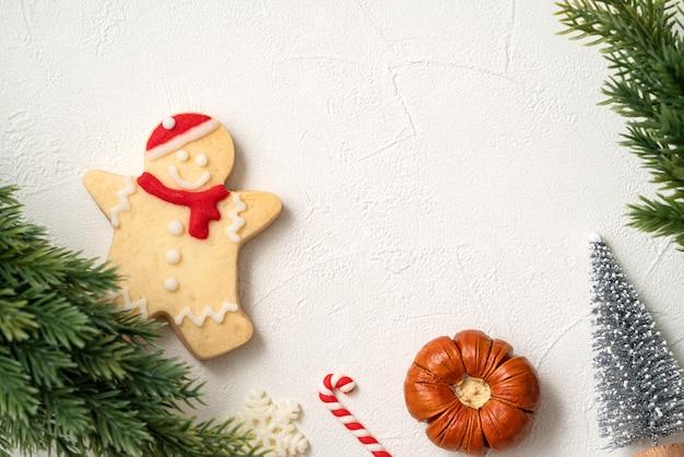 コピースペース、休日のお祝いの概念と白いテーブルの背景に装飾が施された装飾されたクリスマスジンジャーブレッドクッキーの上面図。