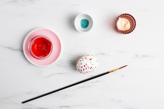 Вид сверху украшенного пасхального яйца на тарелке с краской и кистью