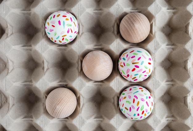 Вид сверху украшенных пасхальных яиц в картонной коробке