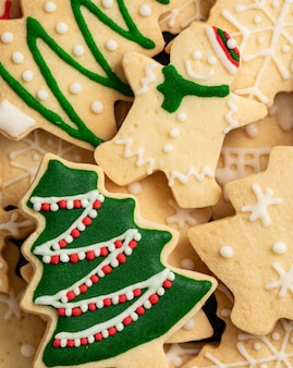 コピースペース、休日のお祝いのコンセプトと装飾された緑のプレーンフレーバージンジャーブレッドクリスマスツリークッキーの上面図。