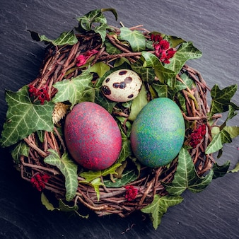 Вид сверху на декоративное птичье гнездо с крашеными пасхальными яйцами