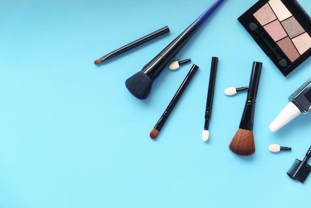 青い背景の上の装飾的な黒い色の化粧品の上面図