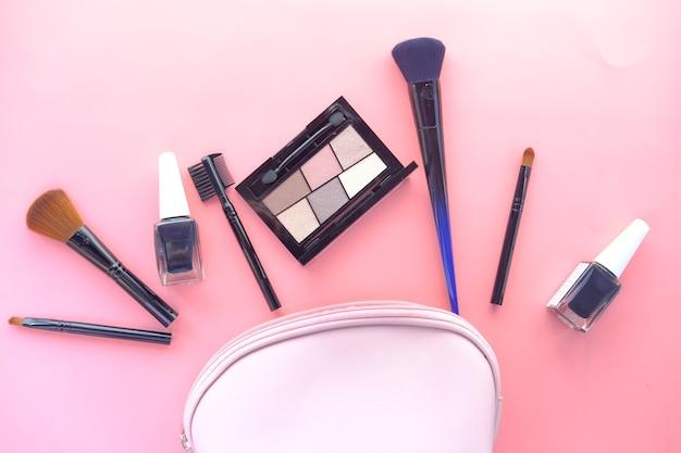 ピンクの机の上の装飾的な黒い色の化粧品の上面図。