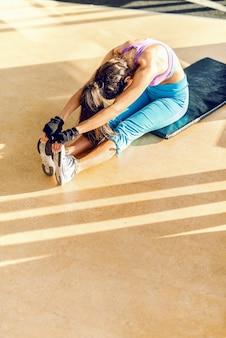床に伸びるスポーツウェアに身を包んだポニーテールの専用女性の平面図です。ジムのインテリア。