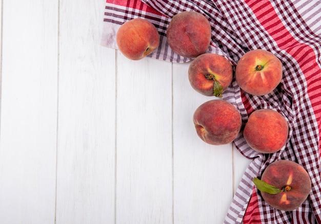Вид сверху вкусных и свежих персиков на скатерти в клетку на белом с копией пространства