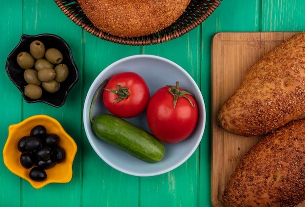 Вид сверху вкусных и кунжутных котлет на деревянной кухонной доске с помидорами и огурцами на миске с оливками на зеленом деревянном фоне
