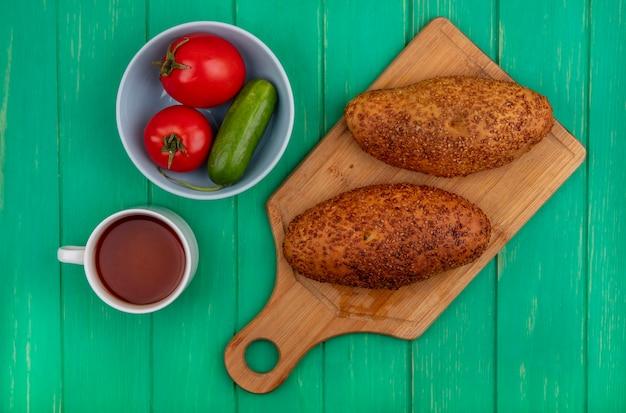 Вид сверху вкусных и кунжутных котлет на деревянной кухонной доске с овощами на миске на зеленом деревянном фоне