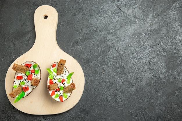 회색 표면에 사워 크림 슬라이스 고추와 빵 조각과 함께 맛있는 아보카도 식사의 상위 뷰
