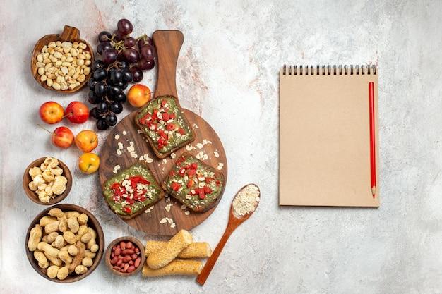 白い表面にブドウとナッツのおいしいアボカドサンドイッチの上面図