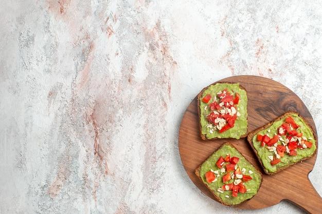 흰색 표면에 얇게 썬 빨간 토마토와 맛있는 아보카도 샌드위치의 상위 뷰