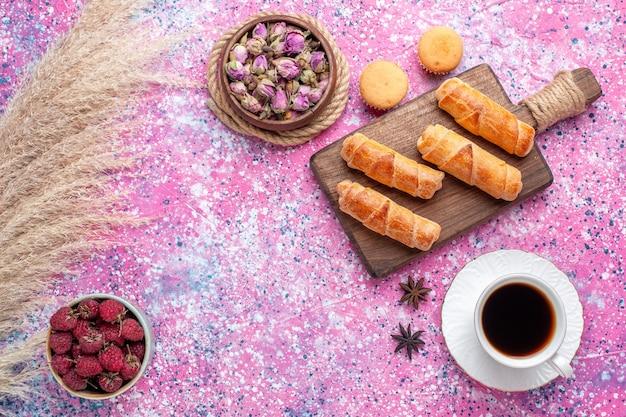 Вид сверху вкусных рогаликов с чашкой чая и фруктами на светло-розовой поверхности
