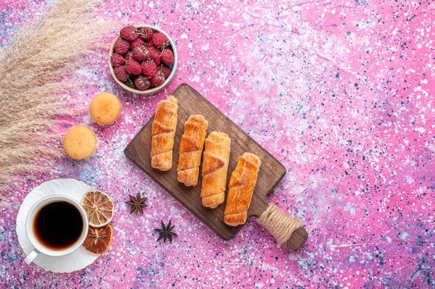 Вид сверху вкусных рогаликов с чашкой чая на розовой поверхности