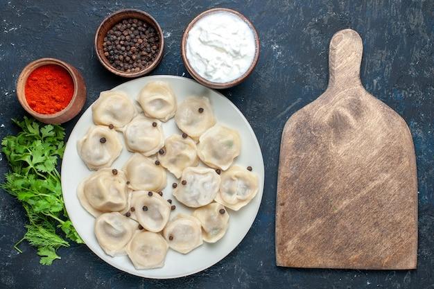 Вид сверху на вкусные запеченные пельмени внутри тарелки вместе с перечным йогуртом и зеленью на темном столе, еда из теста, обед, мясо