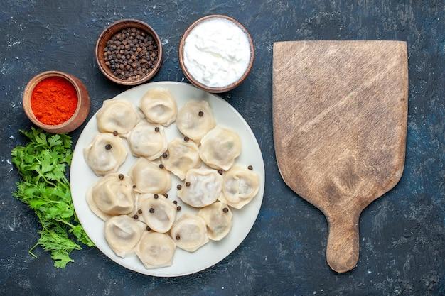 Вид сверху вкусных запеченных пельменей внутри тарелки вместе с перечным йогуртом и зеленью на темной, тесто, обед, ужин, мясная калорийность