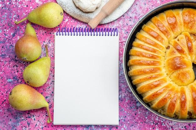 ライトデスクにメモ帳と梨、ペストリークッキービスケットスイートシュガーと鍋の中に形成されたおいしい焼きたてのペストリーバングルの上面図
