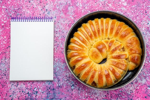 明るい机の上のメモ帳、ペストリークッキービスケット甘い砂糖で鍋の中に形成されたおいしい焼きたてのペストリーバングルの上面図