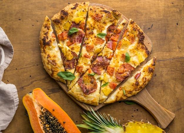 Вид сверху вкусной запеченной пиццы с ананасом и папайей
