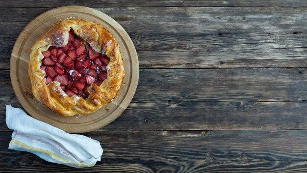 木製のテーブルにイチゴを添えたおいしい焼きたてのタルトのトップ ビュー