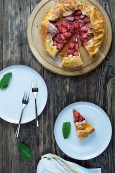 木製のテーブルにプレートとフォークを添えたイチゴのおいしい焼きたてのタルトのトップ ビュー