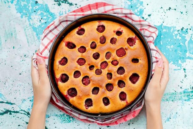 Вид сверху восхитительного ягодного торта, запеченного и вкусного внутри сковороды, которую держит женщина на ярко-синем бисквитном тесте с фруктами, ягодным сладким