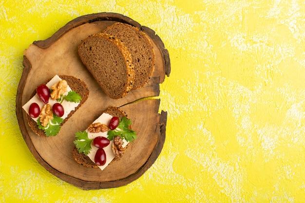 노란색 표면에 층층 치즈와 함께 맛있는 빵 토스트의 상위 뷰