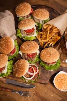 シェフのナイフの横にある木製のタブレットでおいしいハンバーガーの上面図。食品組成