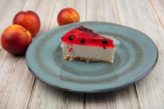 Вид сверху вкусного торта на тарелке со свежими персиками, изолированными на серой деревянной стене
