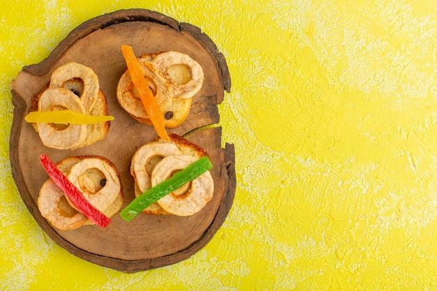 Вид сверху вкусных кусочков торта с мармеладом и кольцами ананаса на желтой поверхности