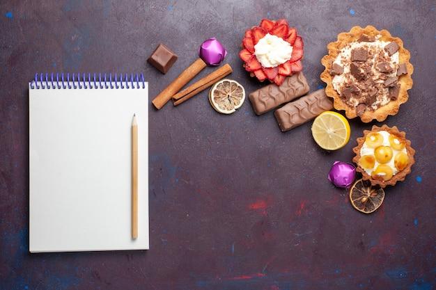 Вид сверху вкусных тортов вместе с блокнотом с корицей и конфетами на темной поверхности