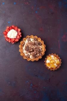暗い表面にクリームとチョコレートのピースが付いたおいしいケーキの上面図