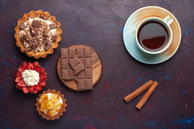 Вид сверху вкусных тортов со сливочным шоколадом и фруктами вместе с чаем на темной поверхности