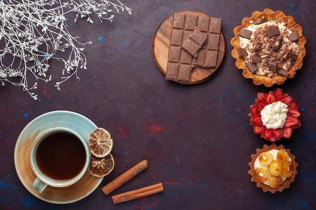 Вид сверху вкусных тортов со сливочным шоколадом и фруктами с чаем на темной поверхности