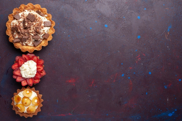 어두운 바닥에 크림 초콜릿과 함께 맛있는 케이크의 상위 뷰 과일 케이크 비스킷 설탕 달콤한 무료 사진