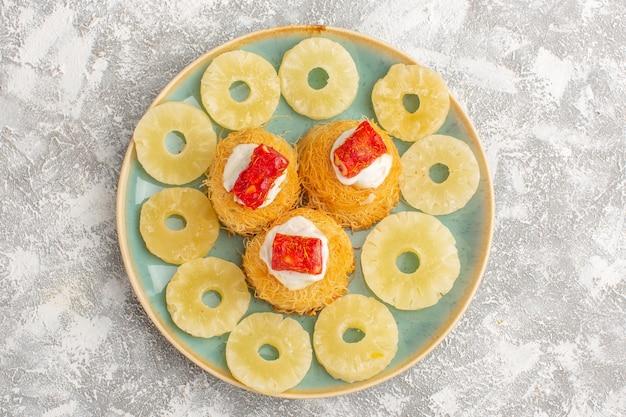 Вид сверху вкусных тортов с белым кремом и красным мармеладом внутри тарелки на светлой поверхности