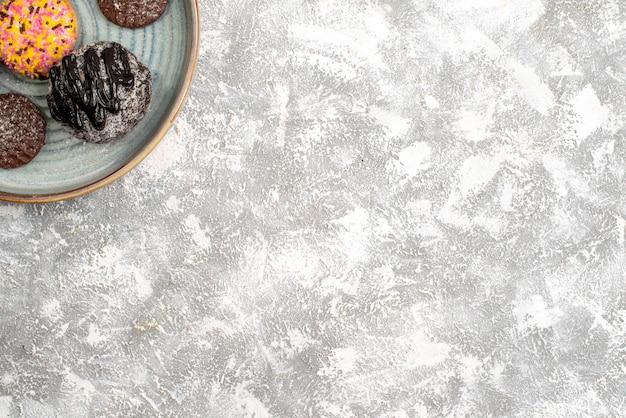 밝은 흰색 표면에 쿠키와 함께 맛있는 초콜릿 볼 케이크의 상위 뷰