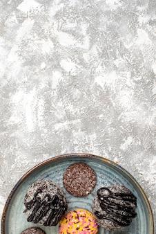 흰색 표면에 쿠키와 함께 맛있는 초콜릿 볼 케이크의 상위 뷰