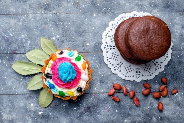 灰色で分離されたクリームケーキで形成されたラウンドのおいしいチョコレートケーキの上面図、焼きチョコレートケーキココアスイートビスケット