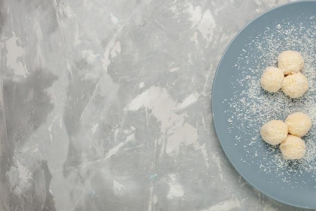 Вид сверху вкусных кокосовых конфет внутри синей тарелки на белом столе