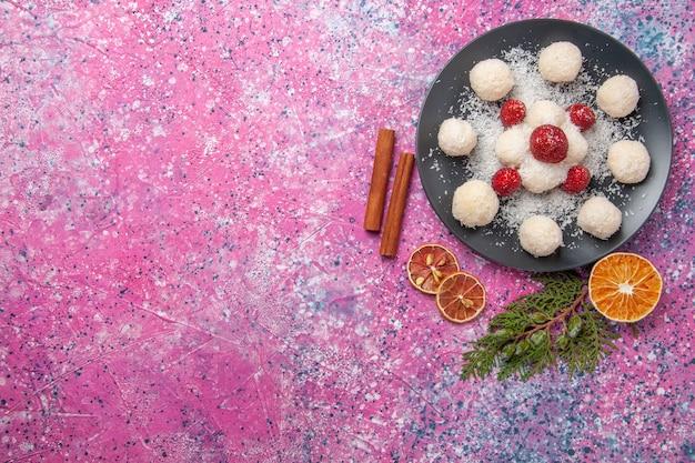 ピンクの表面のプレート内のおいしいココナッツキャンディーの上面図