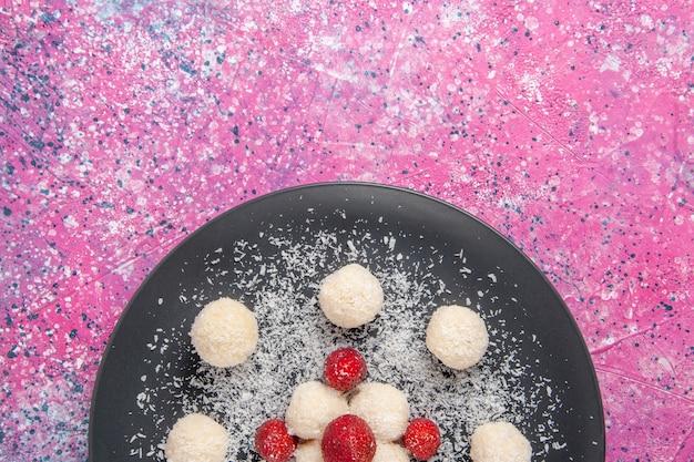 Вид сверху вкусных кокосовых конфет, сладких шариков на розовой поверхности