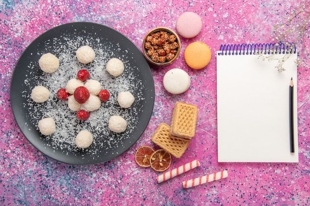 Вид сверху вкусных кокосовых конфет, сладких шариков с французскими макаронами и вафлями на розовом столе