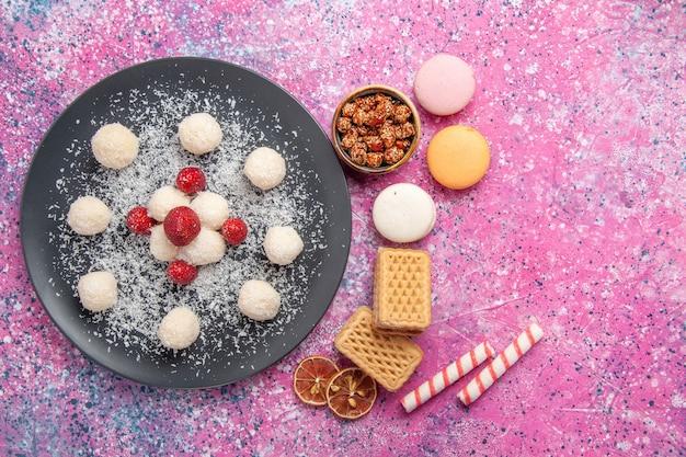 Вид сверху вкусных кокосовых конфет, сладких шариков с французскими макаронами и вафлями на розовой поверхности