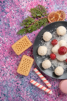 Вид сверху вкусных кокосовых конфет, сладких шариков с вафлями и макаронами на розовой поверхности
