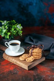 Вид сверху на вкусный кофе в белой чашке и домашнее сахарное печенье на коричневом деревянном цветочном горшке на фоне темных цветов со свободным пространством