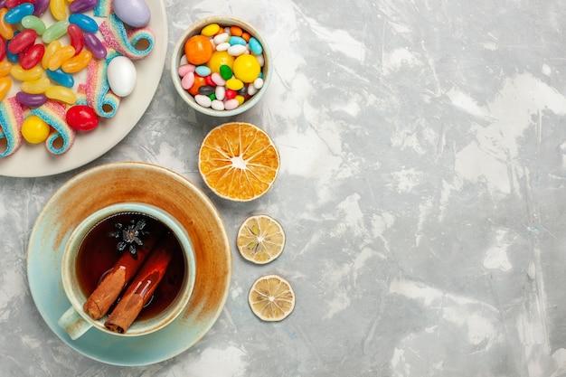 白い表面にマーマレードとお茶のカップとおいしいカラフルなキャンディーの上面図